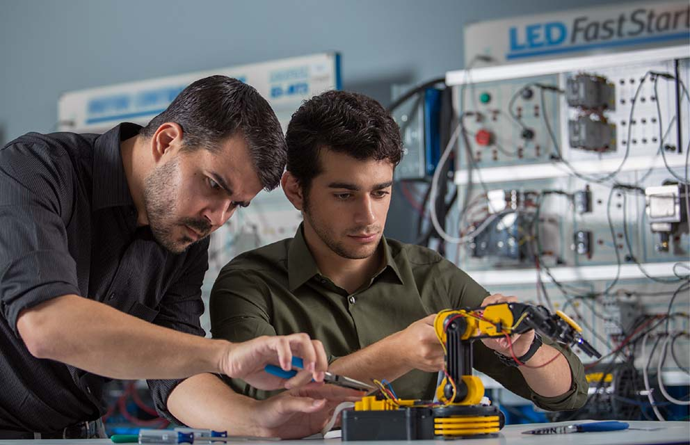 Two men working on robot