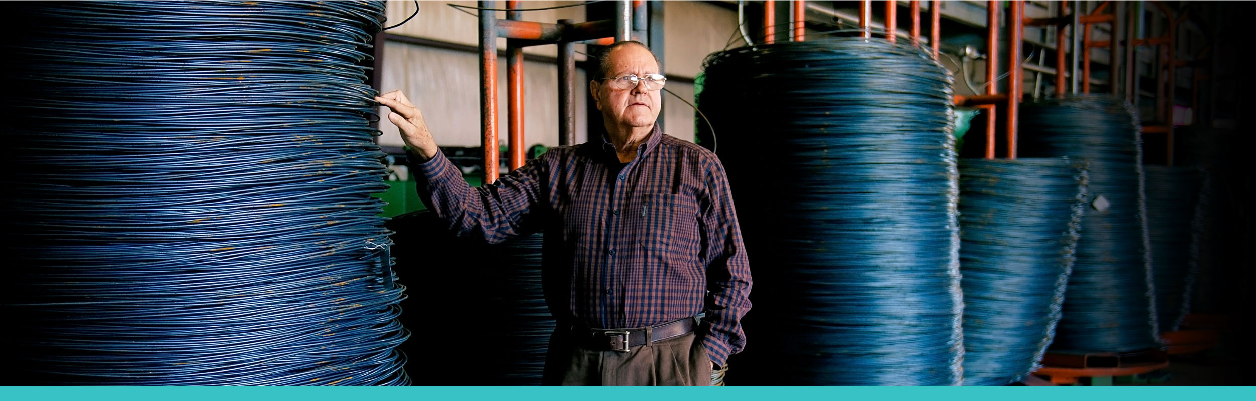 Man standing next to wire coils